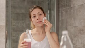 woman Cleansing, toning and moisturizing her face